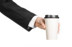 Tema del caffè dei pranzi di lavoro: uomo d'affari in un vestito nero che tiene una tazza di caffè bianca della carta in bianco c Fotografie Stock