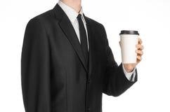 Tema del caffè dei pranzi di lavoro: uomo d'affari in un vestito nero che tiene una tazza di caffè bianca della carta in bianco c Immagine Stock