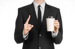 Tema del caffè dei pranzi di lavoro: uomo d'affari in un vestito nero che tiene una tazza di caffè bianca della carta in bianco c Immagine Stock Libera da Diritti