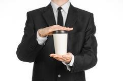 Tema del caffè dei pranzi di lavoro: uomo d'affari in un vestito nero che tiene una tazza di caffè bianca della carta in bianco c Fotografia Stock