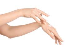 Tema del cuidado de la salud y del cuerpo: mano femenina hermosa con la crema blanca aislada en un fondo blanco, masaje de la man imagen de archivo