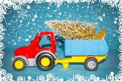 Tema del día de fiesta de la celebración de Navidad Árbol de navidad que lleva del tractor en remolque en fondo de las nevadas Fotos de archivo libres de regalías