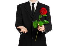 Tema del día de tarjeta del día de San Valentín y del día de las mujeres: la mano del hombre en un traje que sostiene una rosa ro Foto de archivo