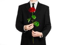 Tema del giorno delle donne e di San Valentino: la mano dell'uomo in un vestito che giudica una rosa rossa isolata su fondo bianc Immagini Stock Libere da Diritti