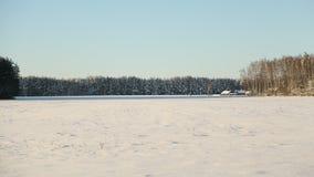 Tema del invierno Campo y bosque en la nieve en tiempo soleado y gran paisaje de la helada de un pequeño pueblo o del pueblo Foto de archivo libre de regalías