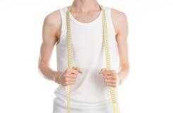 Tema del levantamiento de pesas y de los deportes: un hombre fino en una camiseta blanca y vaqueros con la cinta métrica aislada  Imagen de archivo