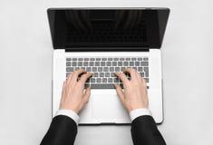Tema del negocio y de la tecnología: la mano del hombre en un traje negro que muestra gesto contra un ordenador portátil gris y b Foto de archivo libre de regalías