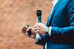 Tema del negocio y del discurso: Sirva en un traje azul que sostiene un micrófono gris a en un fondo anaranjado de los ladrillos Imagen de archivo libre de regalías