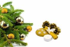 Tema del nuovo anno: Albero di Natale, palle dorate, decorazioni, candela, fiocchi di neve, biscotti, coni, cannella isolata Fotografia Stock Libera da Diritti