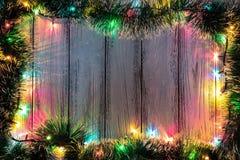 Tema del nuovo anno: decorazione e ghirlanda dell'albero di Natale con le luci colorate su fondo di legno stilizzato bianco Immagini Stock