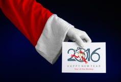 Tema 2016 del nuovo anno e di Natale: Mano di Santa Claus che giudica una carta di regalo bianca su un fondo blu scuro in studio  Fotografie Stock