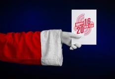 Tema 2016 del nuovo anno e di Natale: Mano di Santa Claus che giudica una carta di regalo bianca su un fondo blu scuro in studio  Immagine Stock Libera da Diritti