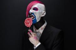 Tema del payaso y de Halloween: Payaso asustadizo con el pelo rosado en una chaqueta negra con el caramelo a disposición en un fo Imagenes de archivo