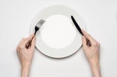 Tema del restaurante y de la comida: el gesto humano de la demostración de la mano en una placa blanca vacía en un fondo blanco e Imagen de archivo