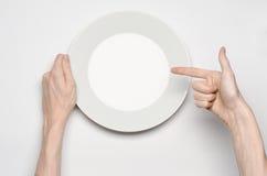 Tema dell'alimento e del ristorante: il gesto umano di manifestazione della mano su un piatto bianco vuoto su un fondo bianco in  Fotografia Stock Libera da Diritti