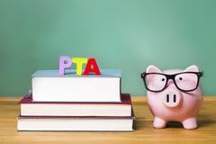 Tema della PTA con il porcellino salvadanaio rosa con la lavagna Immagini Stock Libere da Diritti
