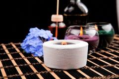 Tema della stazione termale con le candele ed i fiori su fondo nero fotografie stock