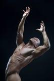 Tema della striscia e del culturista: bello con l'uomo nudo pompato dei muscoli che posa nello studio su un fondo scuro Fotografie Stock Libere da Diritti