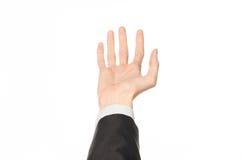 Tema di affari e di gesti: l'uomo d'affari mostra i gesti di mano con un in prima persona in un vestito nero su un fondo bianco i Immagine Stock