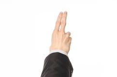 Tema di affari e di gesti: l'uomo d'affari mostra i gesti di mano con un in prima persona in un vestito nero su un fondo bianco i Fotografia Stock Libera da Diritti