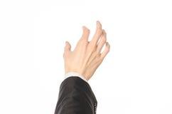 Tema di affari e di gesti: l'uomo d'affari mostra i gesti di mano con un in prima persona in un vestito nero su un fondo bianco i Fotografie Stock