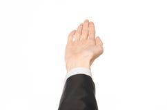 Tema di affari e di gesti: l'uomo d'affari mostra i gesti di mano con un in prima persona in un vestito nero su un fondo bianco i Fotografia Stock