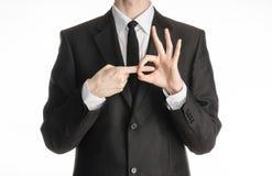 Tema di affari e di gesti: l'uomo d'affari mostra i gesti di mano con un in prima persona in un vestito nero su un fondo bianco i Immagini Stock