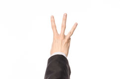 Tema di affari e di gesti: l'uomo d'affari mostra i gesti di mano con un in prima persona in un vestito nero su un fondo bianco i Immagini Stock Libere da Diritti