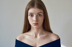 Tema di bellezza: ritratto di bella ragazza con le lentiggini sul suo fronte e sul portare un vestito blu su un fondo bianco in s Immagini Stock Libere da Diritti
