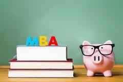 Tema di grado di MBA con i manuali ed il porcellino salvadanaio Fotografia Stock Libera da Diritti
