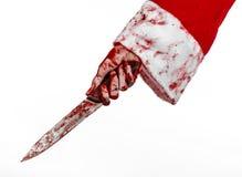 Tema di Halloween e di Natale: Le mani sanguinose di Santa di un pazzo che tiene un coltello sanguinoso su un fondo bianco isolat Immagini Stock