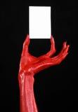 Tema di Halloween: Mano del diavolo rosso con i chiodi neri che tengono una carta bianca in bianco su un fondo nero Immagine Stock Libera da Diritti
