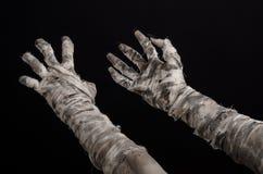 Tema di Halloween: vecchie mani terribili della mummia su un fondo nero Fotografie Stock