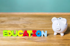 Tema di istruzione con il porcellino salvadanaio bianco e la lavagna verde Immagini Stock Libere da Diritti