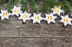 Tema di Natale: stelle calde accoglienti della ghirlanda delle luci e rami dell'abete su fondo di legno rustico Vista superiore s fotografia stock