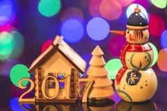 Tema di nuovo anno le figure da 2017 anni con la casa, l'albero di abete ed il pupazzo di neve decorativi sul fondo delle luci Fotografia Stock