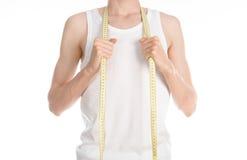 Tema di sport e di culturismo: un uomo sottile in maglietta bianca e jeans con nastro adesivo di misurazione isolato su un fondo  Fotografia Stock Libera da Diritti