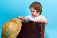 Tema di viaggio del ragazzo del bambino con un suitecase e un cappello fotografie stock