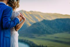 Tema do casamento, guardando rec?m-casados das m?os com uma vista perfeita das montanhas e do rio fotos de stock royalty free