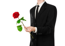 Tema do dia de Valentim e do dia das mulheres: a mão do homem em um terno que mantém uma rosa vermelha isolada no fundo branco no Imagens de Stock Royalty Free