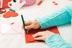 Tema do dia do ` s do Valentim As mãos fêmeas cortaram o coração fora do pap Imagens de Stock