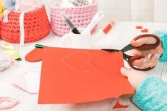 Tema do dia do Valentim As mãos fêmeas cortaram o coração fora do pap Imagem de Stock Royalty Free