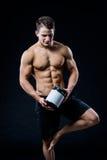 Tema do halterofilismo e dos esportes: halterofilista forte considerável que guarda o frasco plástico com uma proteína seca que s fotos de stock