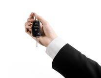 Tema do negócio: vendedor de carro em um terno preto que mantém uma chave do carro isolada no fundo branco Imagens de Stock