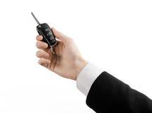Tema do negócio: vendedor de carro em um terno preto que mantém uma chave do carro isolada no fundo branco Fotografia de Stock
