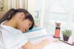 Tema educativo: scolara che dorme sui suoi manuali nella casa Immagini Stock Libere da Diritti