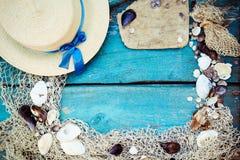 Tema för bakgrund för avkoppling för sommarsemester med snäckskal, fisknät, hatten, repet, stenar och riden ut träblåttbakgrund m Fotografering för Bildbyråer