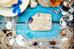 Tema för bakgrund för avkoppling för sommarsemester med snäckskal, fisknät, hatten, repet, stenar och riden ut träblåttbakgrund m Arkivbilder