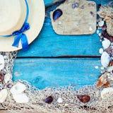 Tema för bakgrund för avkoppling för sommarsemester med snäckskal, fisknät, hatten, repet, stenar och riden ut träblåttbakgrund m Arkivbild
