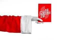 Tema 2016 för jul och för nytt år: Santa Claus hand som rymmer ett rött gåvakort på en vit bakgrund i studio isolerat Arkivfoto